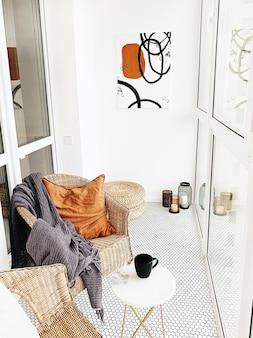 Lichte open ruimte bij loggia met witte muren, rieten stoelen, marmeren tafel, gemberkussen, kaarsen, modern schilderwerk.