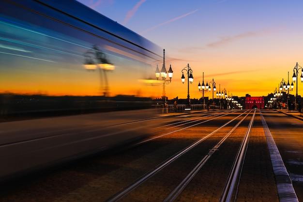 Lichte paden van tram op pont de pierre stenen brug over de rivier de garonne in bordeaux
