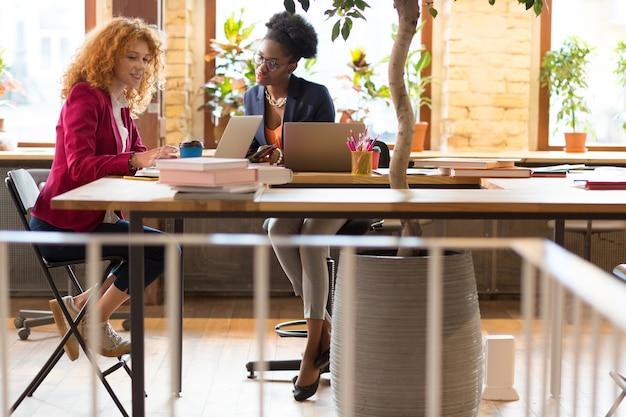Lichte ruime coworking. twee creatieve managers die het druk hebben tijdens het werken in een lichte, ruime coworking