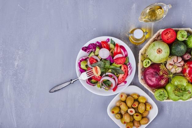 Lichte salade met groenten en kruiden geserveerd met groene olijven.