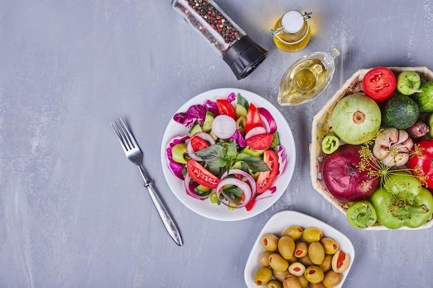 Lichte salade met groenten en kruiden geserveerd met olijfolie.