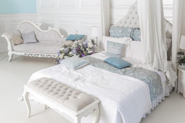 Lichte, schone, stijlvolle slaapkamer en woonkamer met een groot panoramisch raam. prachtige rijke antieke meubelen. hemelbed, een spiegel en een bank.