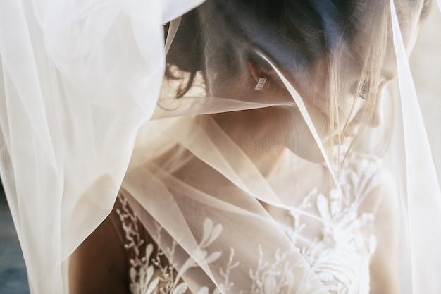 Lichte sluier verbergt tedere jonge bruid