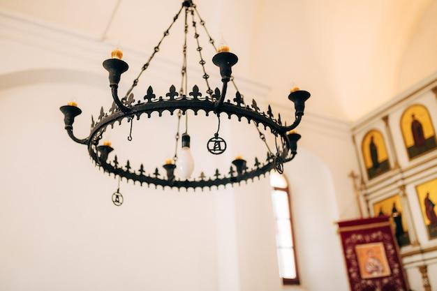 Lichte smeedijzeren kroonluchter van zwart metaal met waskaarsen in de kerk