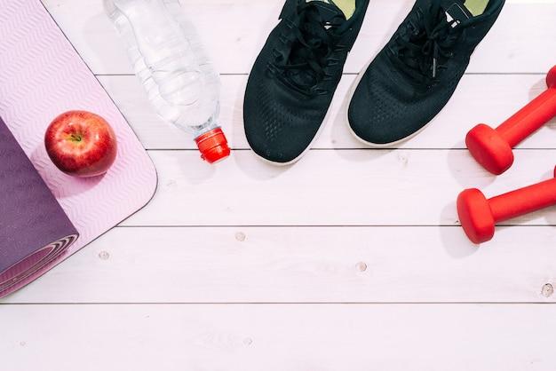 Lichte sportschoenen met dumbbell en yogamat