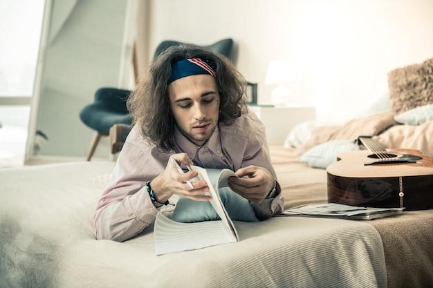 Lichte stijlvolle slaapkamer. attente langharige man met zwarte stoppels die door het album bladert terwijl hij een nieuwe compositie maakt