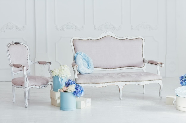 Lichte vintage stijl bank en fauteuil en dozen met bloemen