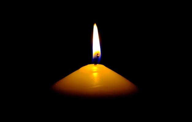 Lichte vlamkaars die fel brandt op zwarte achtergrond