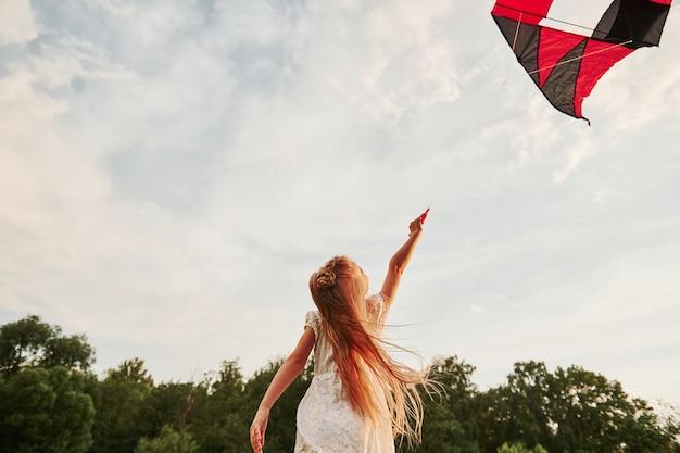 Lichte warme zonneschijn op een kind. gelukkig meisje in witte kleren veel plezier met vlieger in het veld. prachtige natuur. Premium Foto