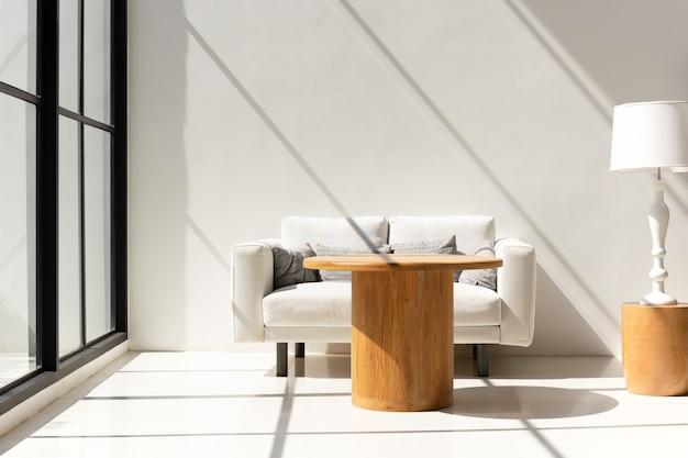 Lichte woonkamer met witte bank en salontafel en lamp.