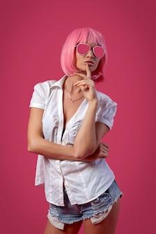 Lichte zomer ontwerpconcept. vrouw in een heldere pruik. close-up van een mooie vrouw in een roze pruik in korte aantrekkelijke jeans, wit overhemd poseren op een roze achtergrond