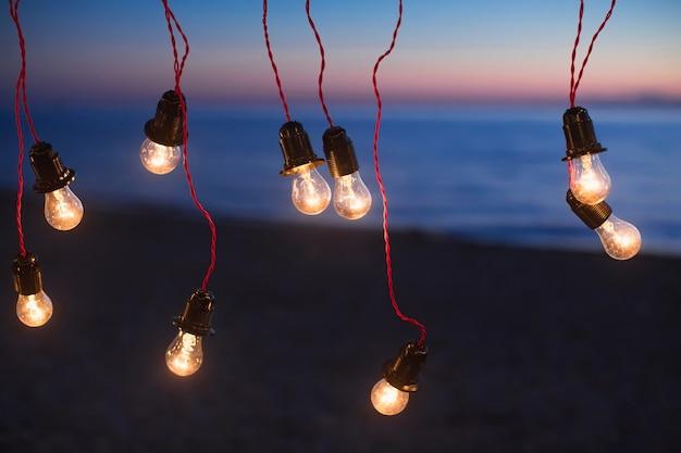 Lichten en lichten 's nachts tegen de achtergrond van de oceaan. bokeh