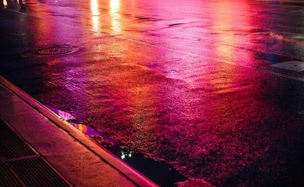 Lichten en schaduwen van new york city. nyc straten na regen met reflecties op nat asfalt. silhouetten van mensen die op straat lopen