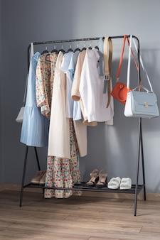 Lichtgekleurde zomerkleding en schoenen voor dames op hanger