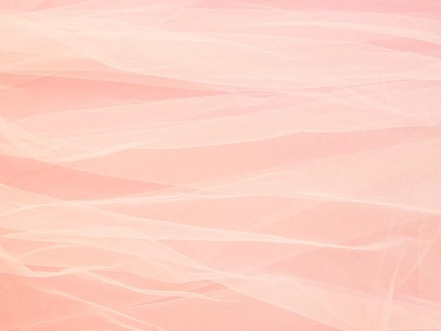 Lichtgewicht gaaskant van stof op roze papier, textuur van de stof is prachtig gedrapeerde achtergrond.