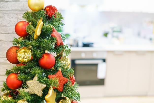 Lichtgrijs keukeninterieur als onscherpe achtergrond en rood met gouden kerstdecor op de boomkok...