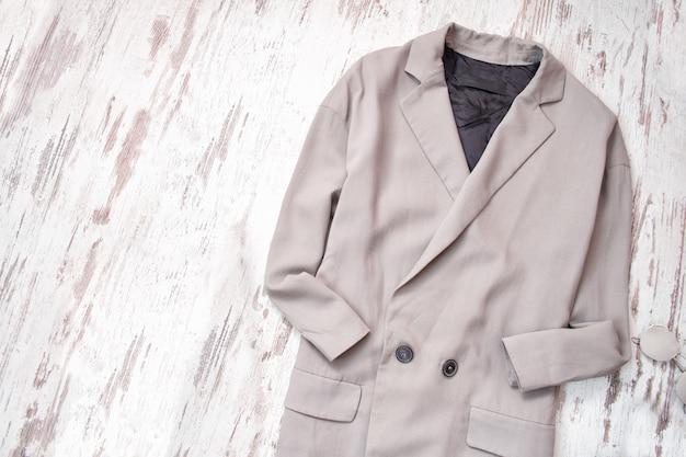 Lichtgrijze jas op een houten achtergrond. mode concept.