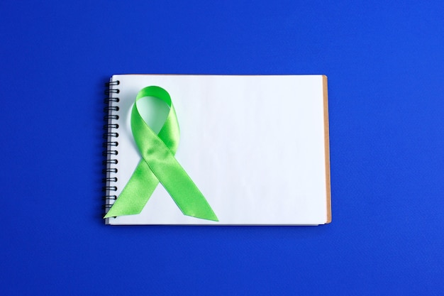 Lichtgroen lint en open notitieblok. leverkanker lymfoombewustzijn. gezondheidszorg en geneeskunde concept.