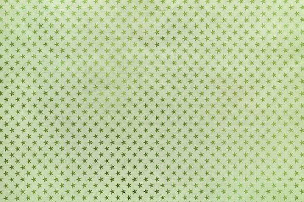 Lichtgroene achtergrond van metaalfoliepapier met een sterrenpatroon