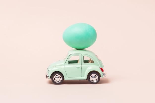 Lichtgroene retro speelgoedauto draagt paasei.