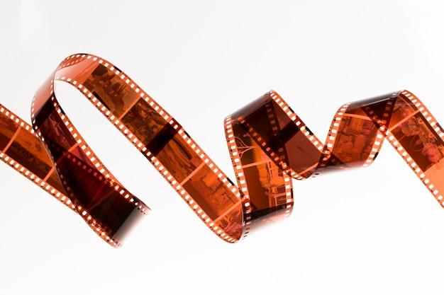 Lichtjes gerolde onontwikkelde filmstrook die op witte achtergrond wordt geïsoleerd
