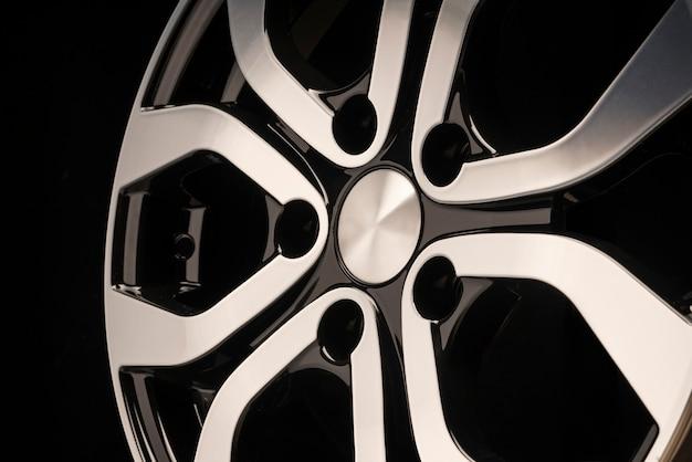 Lichtmetalen wiel voor nieuwe auto, close-up op een zwarte muur, wielelementen, tweekleurige coating, glanzend.