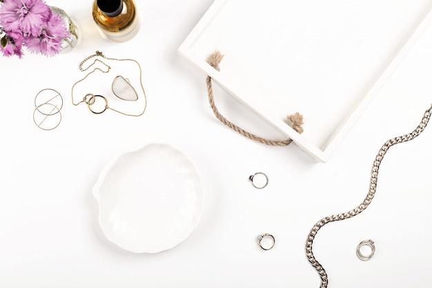 Lichtmodel voor productpresentatie op een witte tafel met damesparfumjuwelen en bloemen op een ...