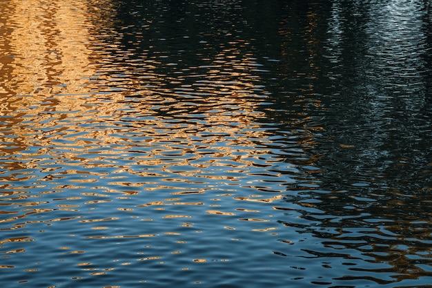 Lichtreflecties op de kleine watergolven van een stedelijke vijver