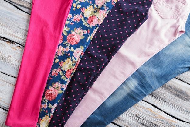 Lichtroze broek en jeans. lichte vrijetijdsbroek voor dames. kledingstukken op witte houten plank. selectie van broeken in boetiek.