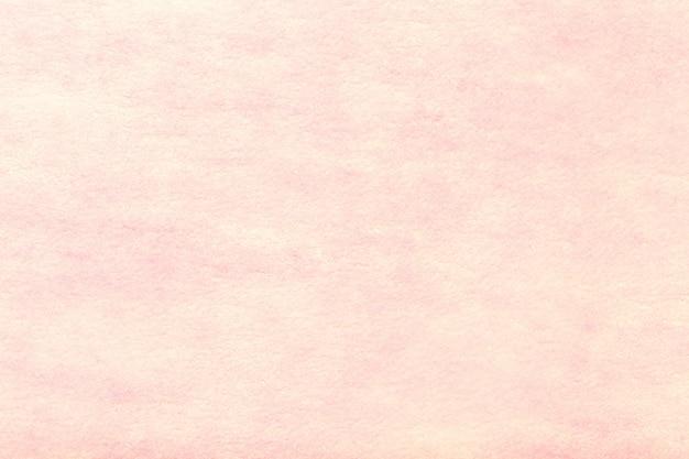 Lichtroze matte suède stoffenachtergrond. fluwelen textuur van vilt.