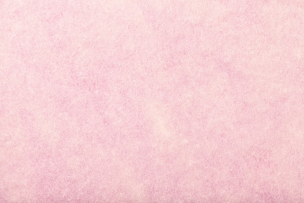 Lichtroze matte suède stoffenclose-up. fluwelen textuur van vilt.