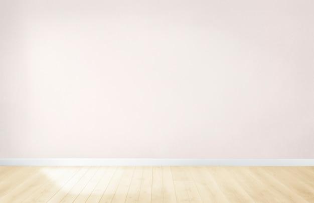 Lichtroze muur in een lege ruimte met een houten vloer