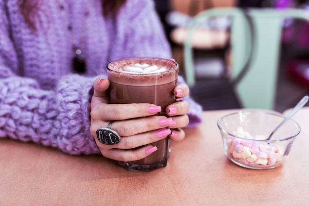 Lichtroze nagels. vrouw in dikke violette trui die vers gemaakte cacao drinkt terwijl ze aan tafel zit