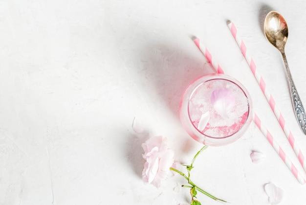 Lichtroze rose cocktail, met rose wijn, thee rozenblaadjes en citroen op een witte stenen betonnen tafel.