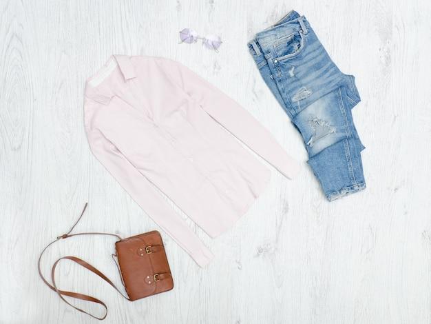 Lichtroze shirt, gescheurde spijkerbroek, handtas en zonnebril. mode concept