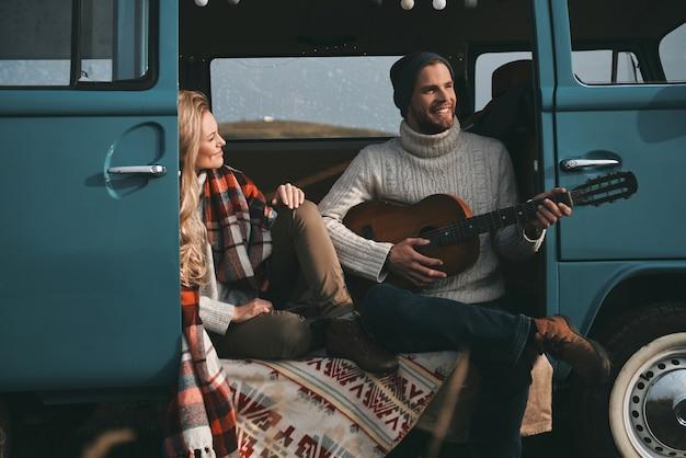 Lied voor haar. knappe jongeman gitaarspelen voor zijn mooie vriendin zittend in blauwe retro-stijl minibusje