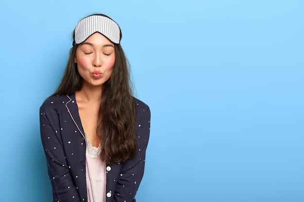 Lief aziatisch meisje draagt slaapmasker, pyjama, houdt lippen rond, ogen dicht, wordt 's ochtends wakker, tevreden na een goede nachtrust