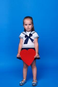 Lief, bedachtzaam jong meisje van 3 jaar oud dat een blauwe jurk draagt, houdt in de hand rood hart geïsoleerd op blauwe muurruimte.