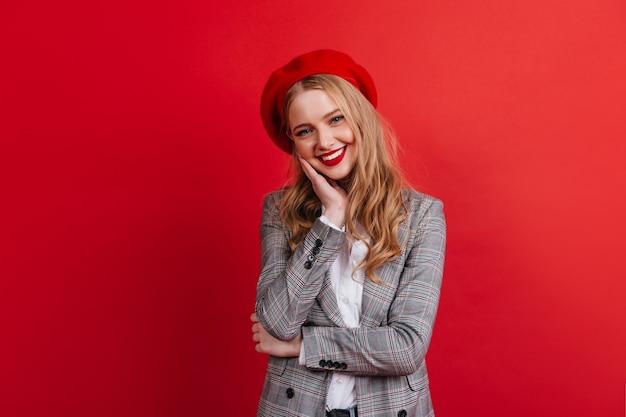 Lief blond meisje in baret. lachende europese vrouw geïsoleerd op rode muur.
