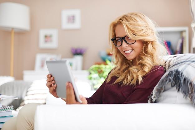 Lief blond meisje met behulp van digitale tablet thuis