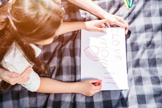 Lief en leuk beeld van meisje liggend op een deken en tekening