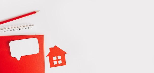 Lief huis. huisbelasting schatten en betalen. bespotten met rood huis, blocnote en sticker op witte achtergrond van de exemplaarruimte