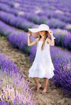 Lief jong meisje in een lavendelveld. een grote hoed en een witte zomerjurk erop.