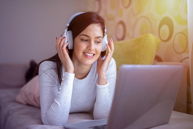 Lief jong meisje liggend op haar bed met een koptelefoon op haar hoofd. naar de muziek luisteren en rusten.