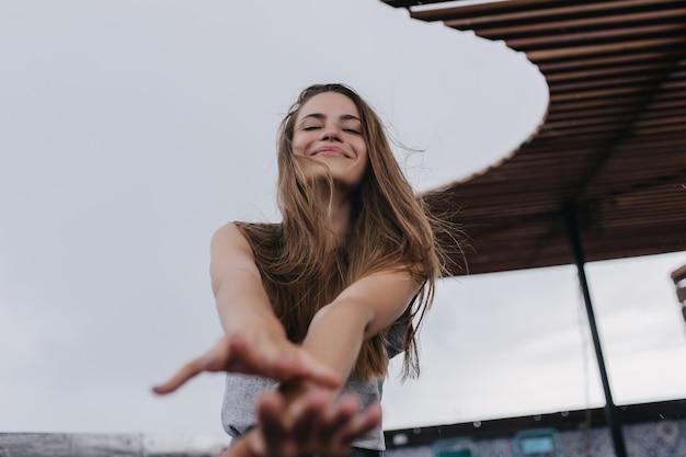 Lief kaukasisch meisje dat positieve emoties uitdrukt. charmante blonde vrouw plezier tijdens het poseren.