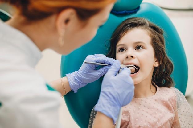 Lief kind dat een tandonderzoek doet door een professionele specialist in een pediatrische stomatologie.