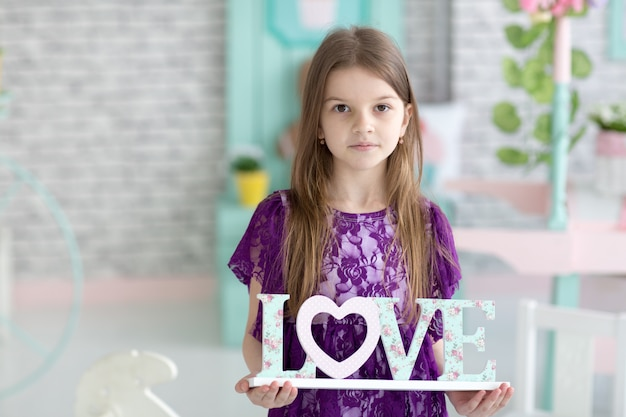 Lief klein donker haarmeisje in purpere kleding in studio