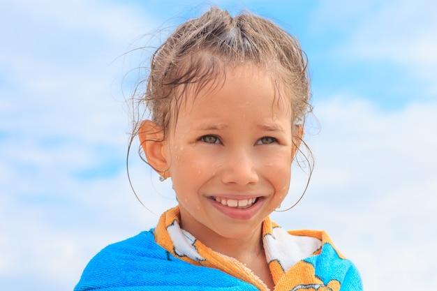 Lief klein meisje drogen na het zwemmen op de hemelachtergrond. reizen vakanties concept.