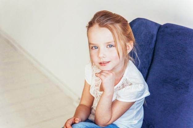 Lief klein meisje in jeans en wit t-shirt zittend op moderne gezellige blauwe stoel ontspannen in witte lichte woonkamer thuis binnenshuis. jeugd schoolkinderen jeugd ontspannen concept.
