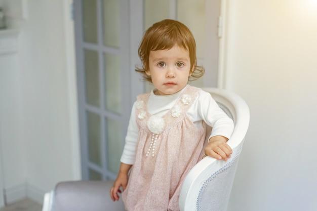 Lief klein meisje in pastel roze jurk thuis zittend op moderne gezellige grijze stoel ontspannen in witte woonkamer. jeugd, kleuterschool, jeugd, ontspannen concept